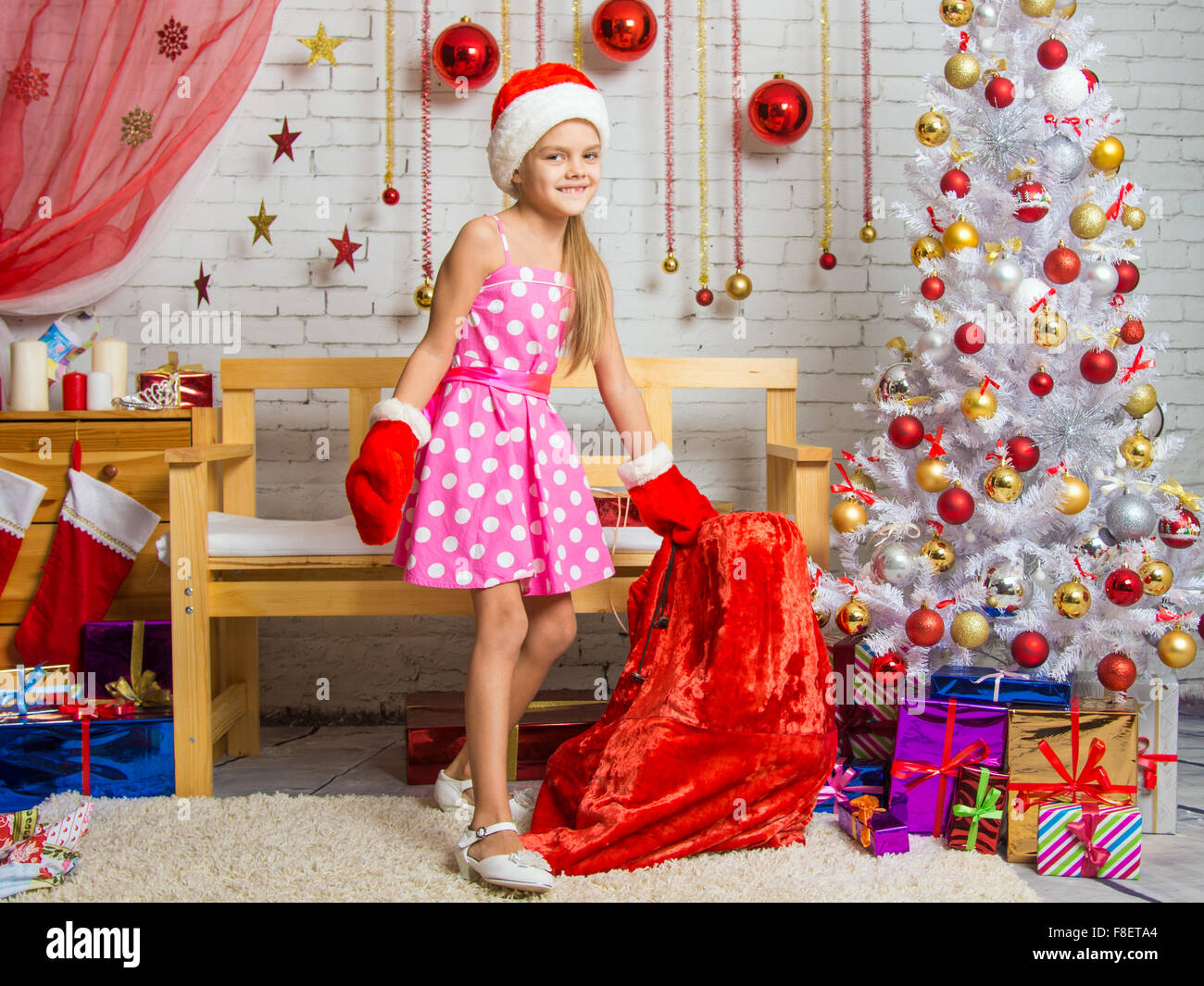 cheerful little girl playing and having fun with a bag of gifts in the home new - What To Get 6 Year Old Little Girl For Christmas