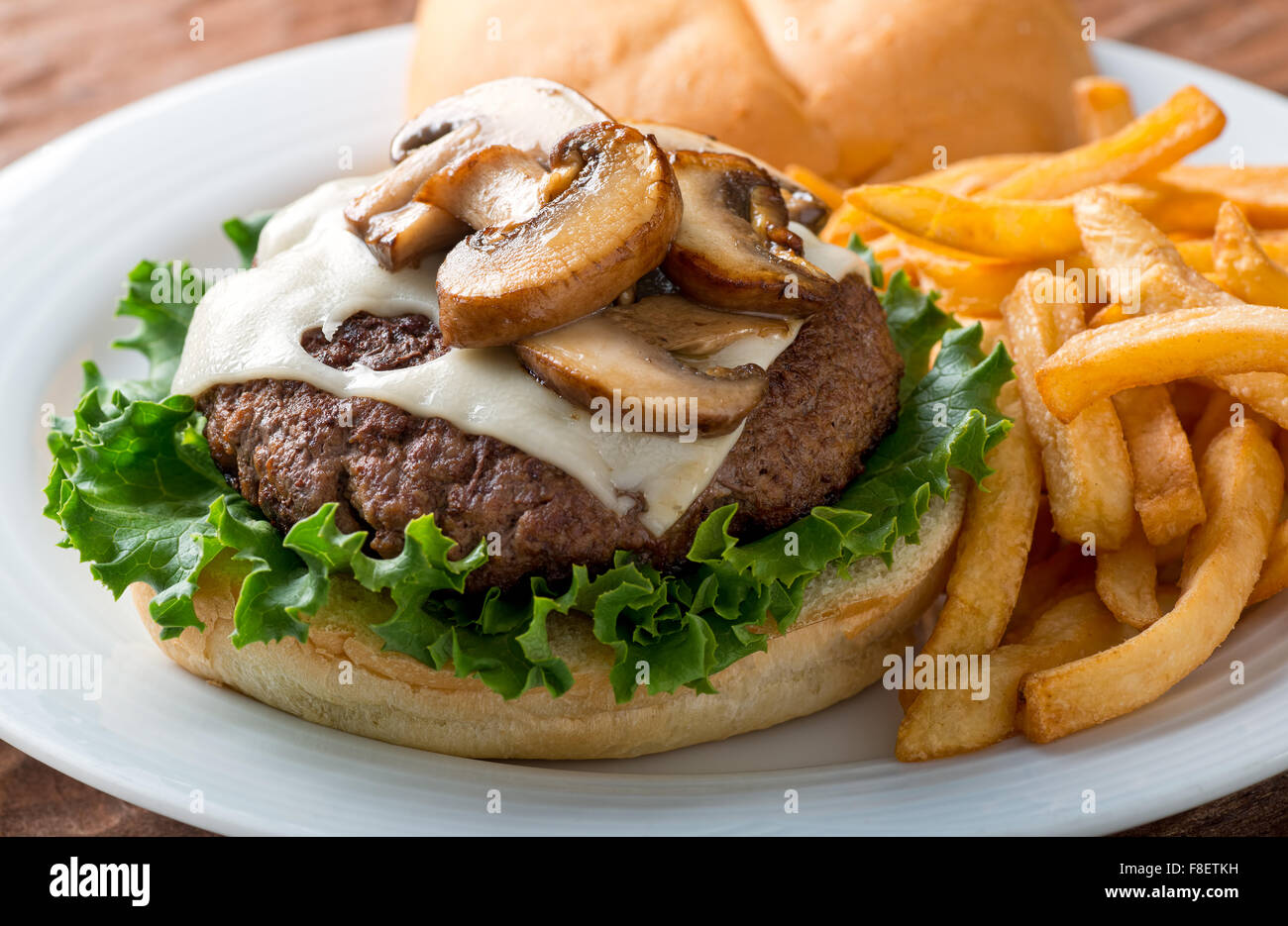 A delicious hamburger topped with swiss cheese and fried mushrooms on a kaiser. - Stock Image