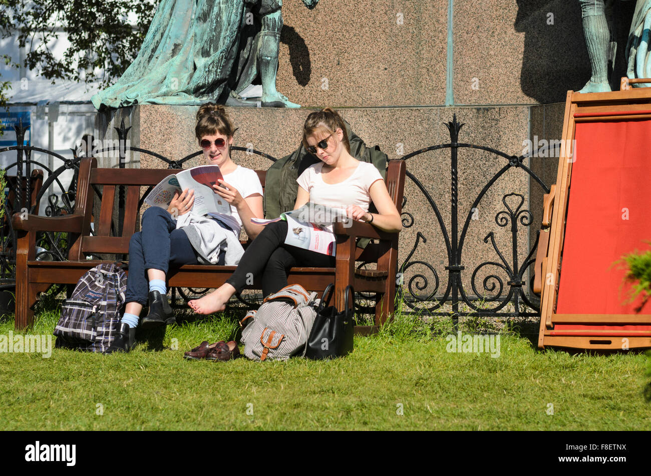 Two young woman relax in the sunshine while reading the program for the 2015 Edinburgh International Book Festival. - Stock Image