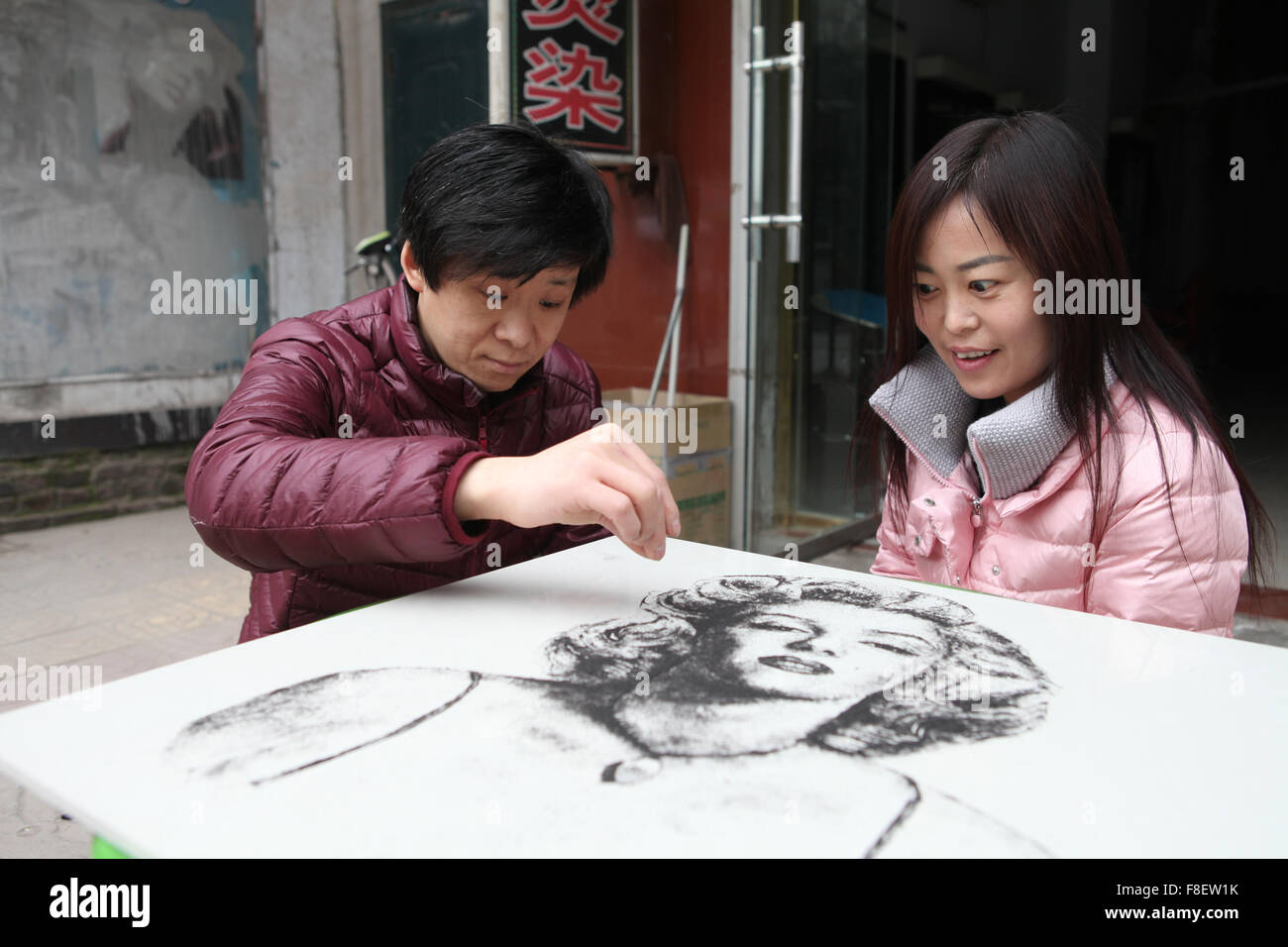 Sanmenxia, China's Henan Province. 9th Dec, 2015. Li Hailiang (L), a 35-year-old barber, draws a picture of - Stock Image