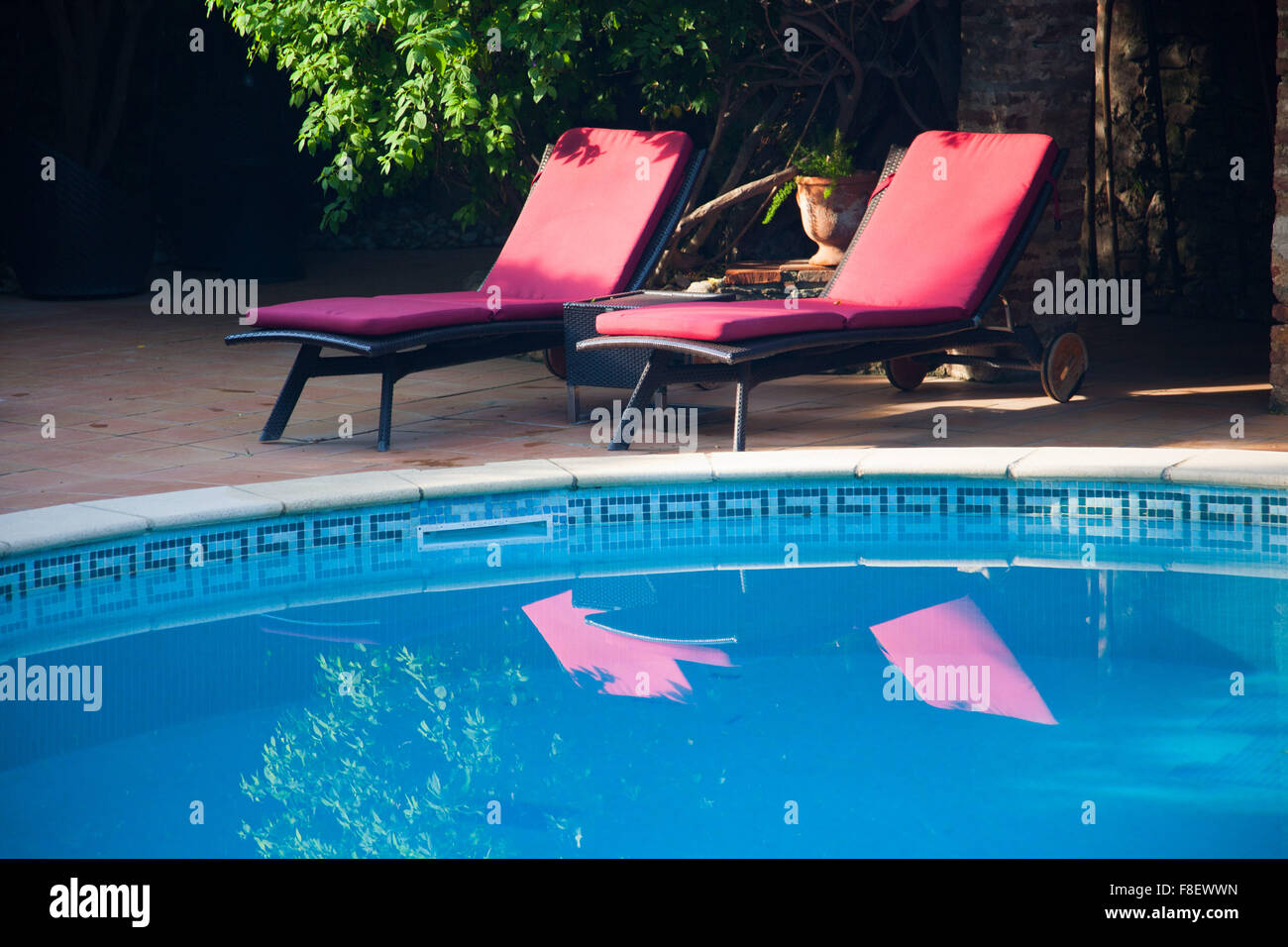 Two red cushioned sun loungers beside a swimming pool - Stock Image
