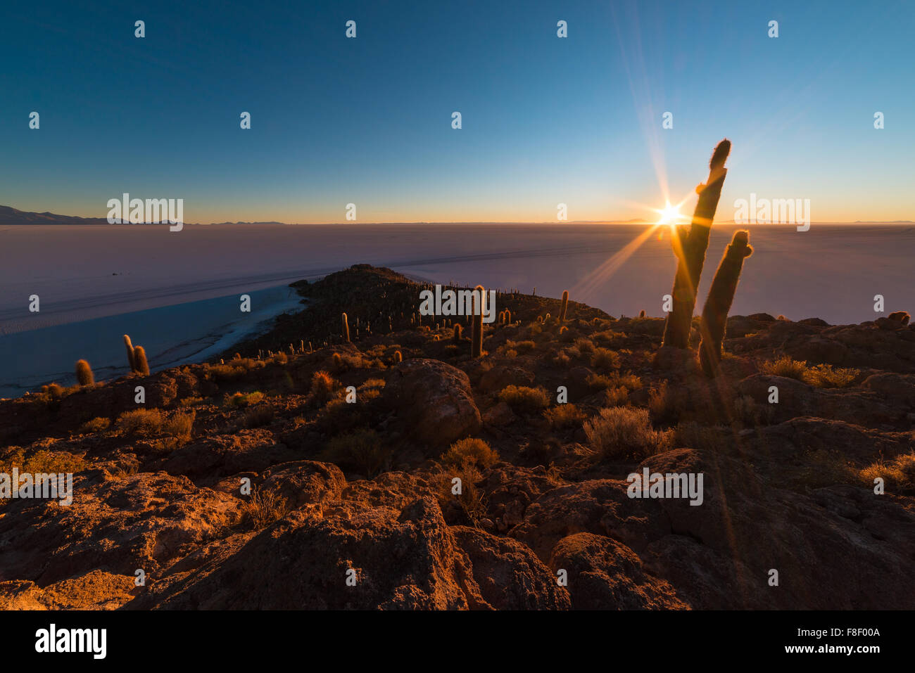 The rising sun at the horizon over the majestic Uyuni Salt Flat, among the most important travel destination in Stock Photo