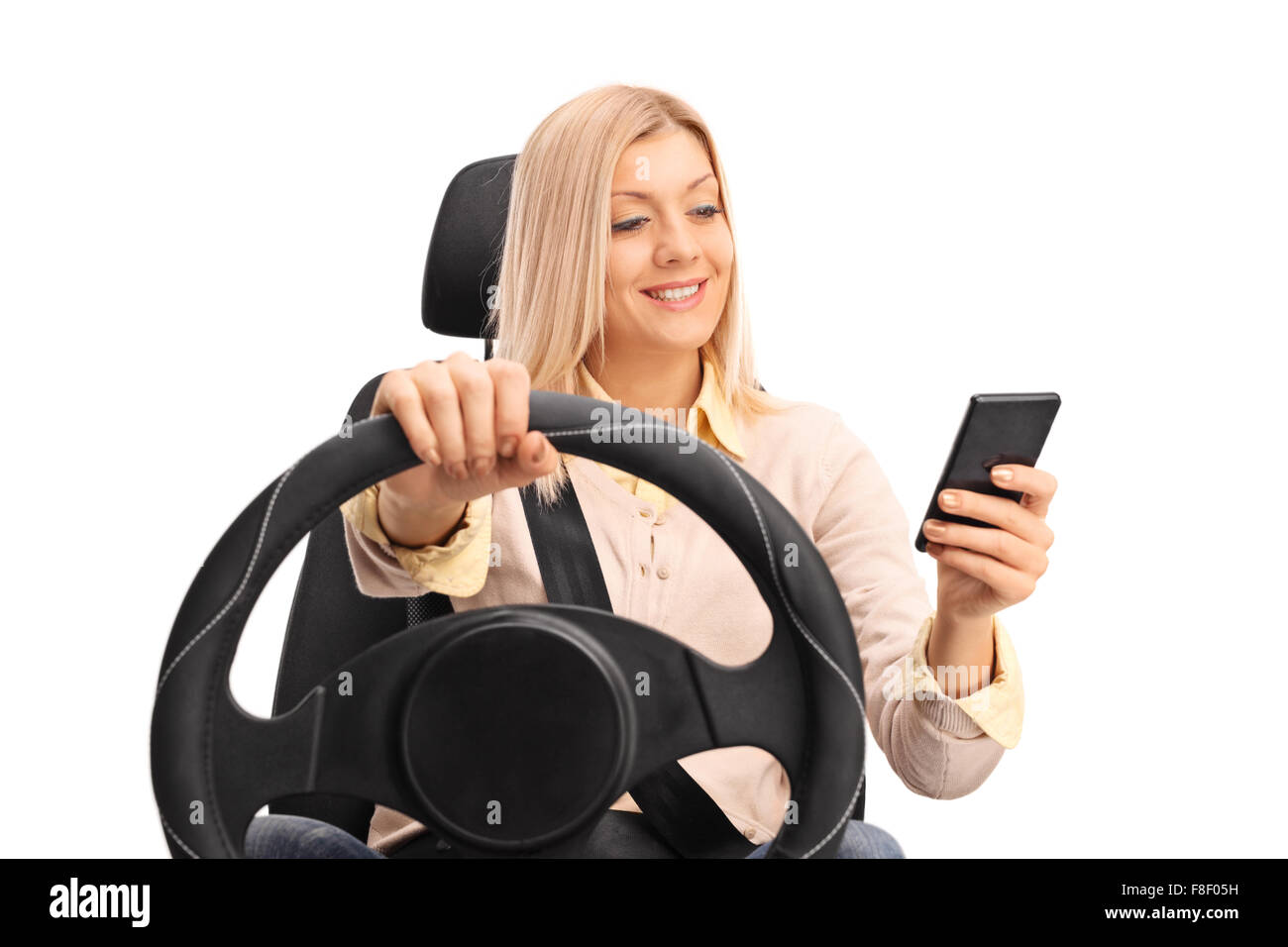 Studio shot of an irresponsible blond woman texting and driving isolated on white background - Stock Image