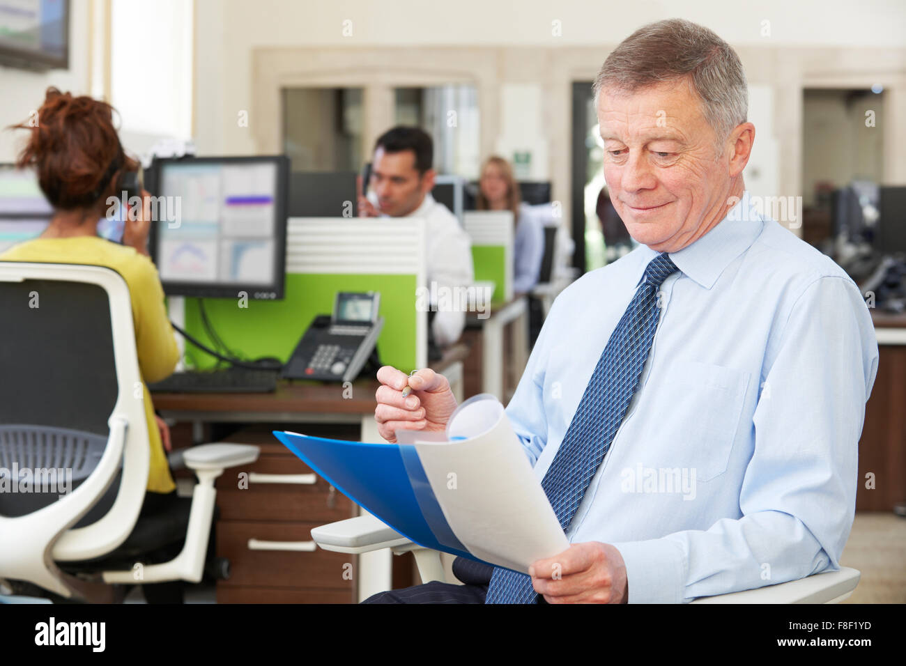 Senior Businessman In Busy Modern Office Stock Photo