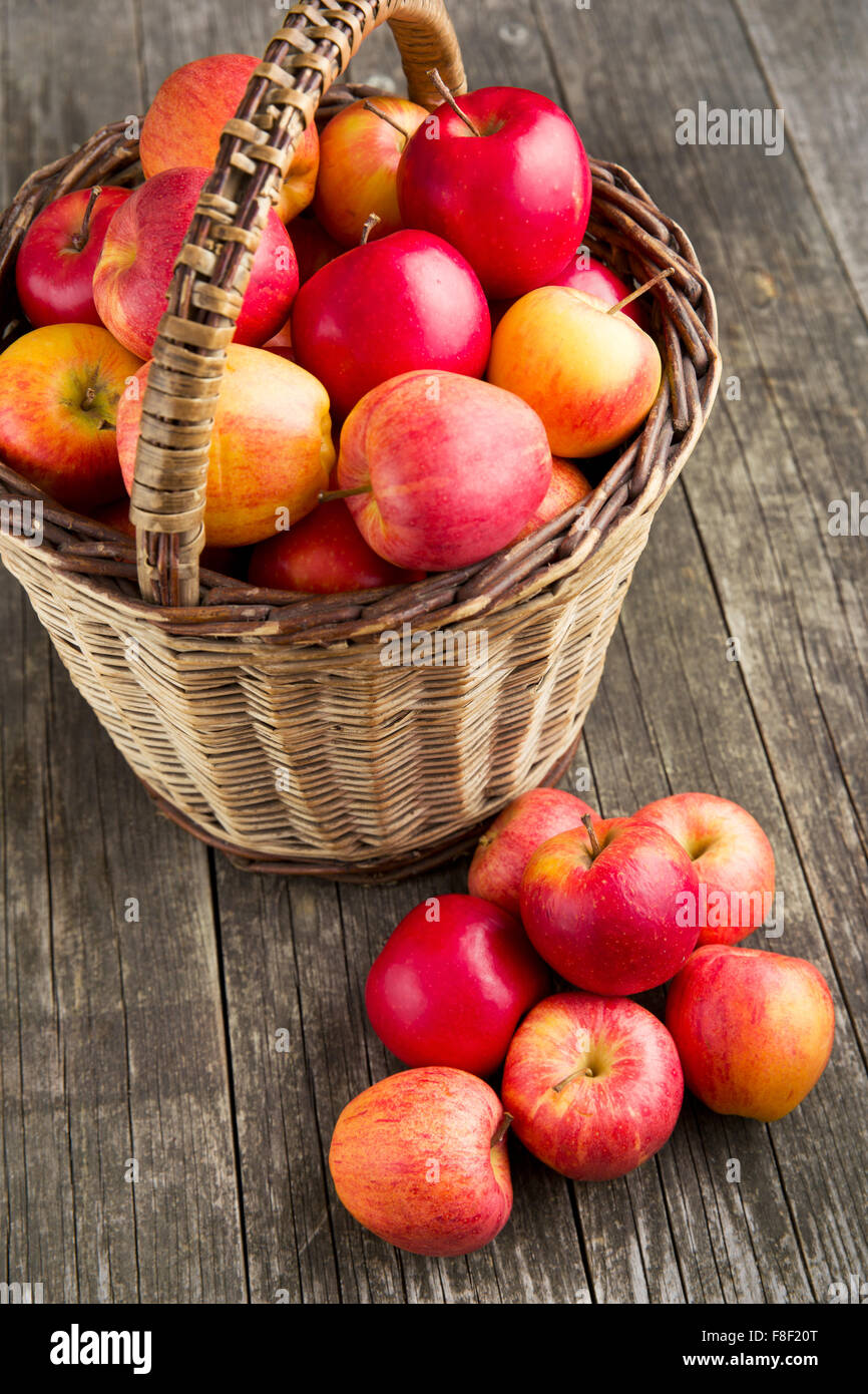 autumn apples in basket on old wooden table - Stock Image