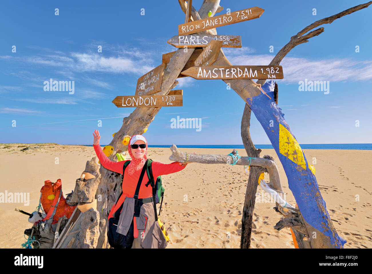 Portugal, Faro: Woman posing with open arms at signal tree in Desert Island - Stock Image