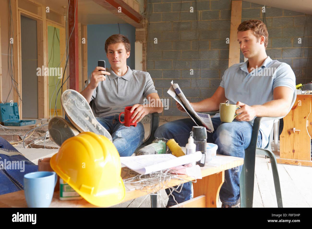 Builders Relaxing During Break On Site - Stock Image