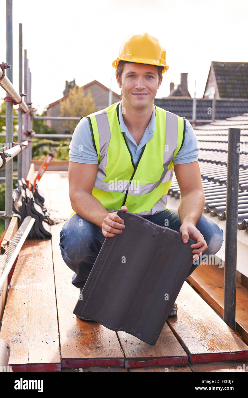 Builder Working On Roof Of New Building - Stock Image