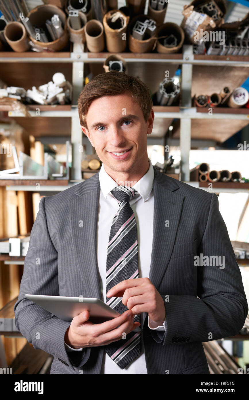 Businessman Checking Stock In Warehouse Using Digital Tablet - Stock Image