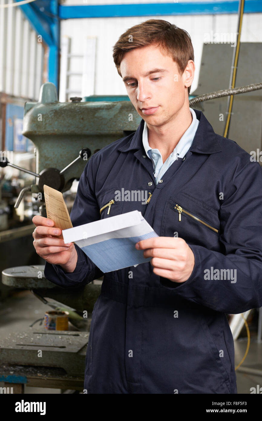 Factory Worker Opening Wage Packet - Stock Image