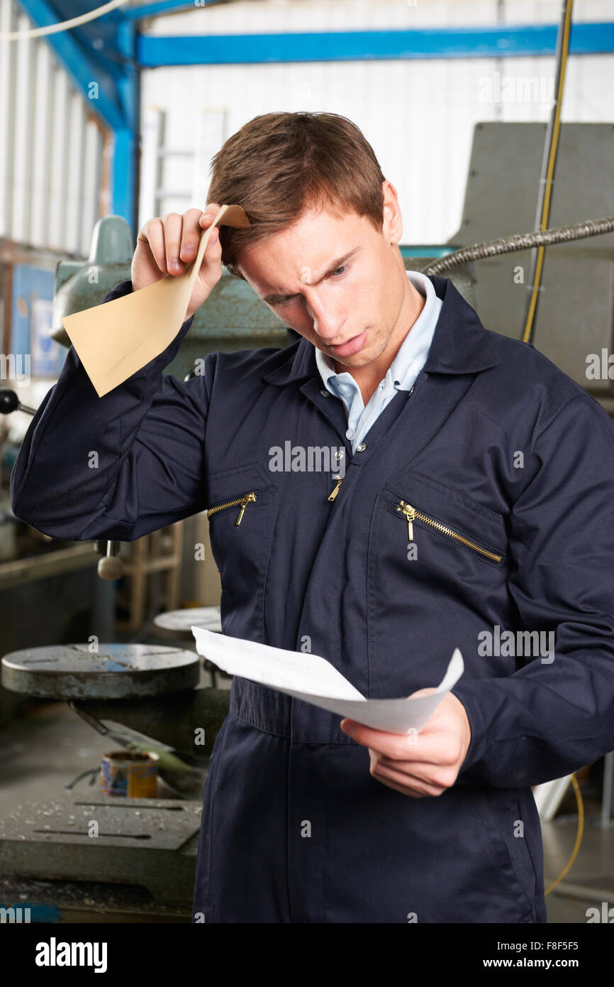 Factory Worker Reading Redundancy Letter - Stock Image
