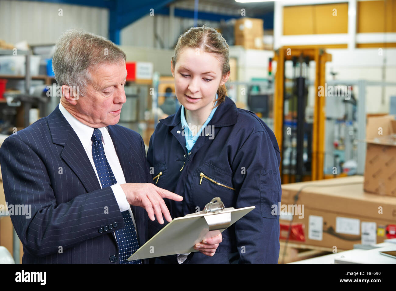 Factory Manager And Apprentice Engineer Looking At Clipboard Stock Photo
