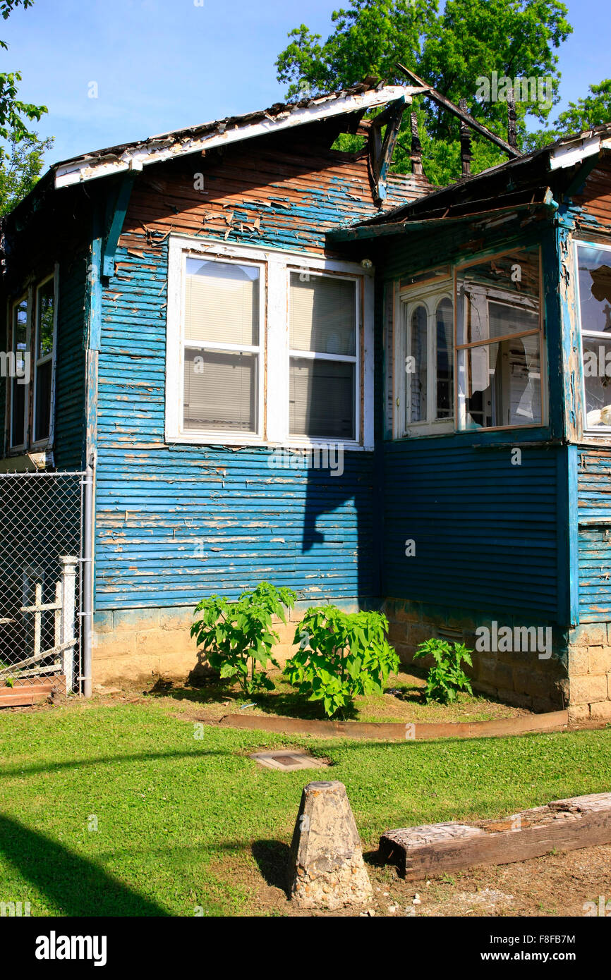 The burnt out shell of a home now surrounded by fencing before it's demolishion - Stock Image