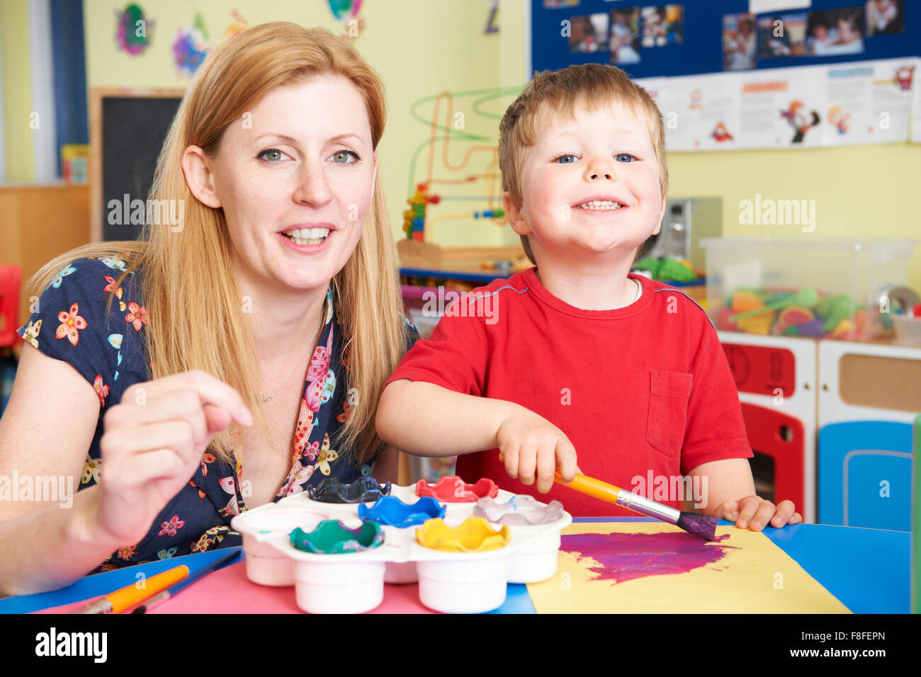 Teacher Helping Preschool Child In Art Class - Stock Image