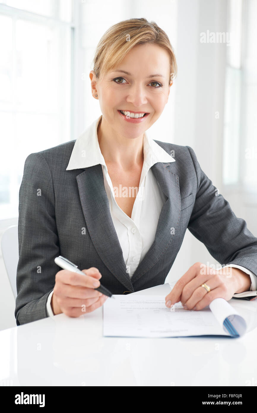 Businesswoman Signing Document - Stock Image
