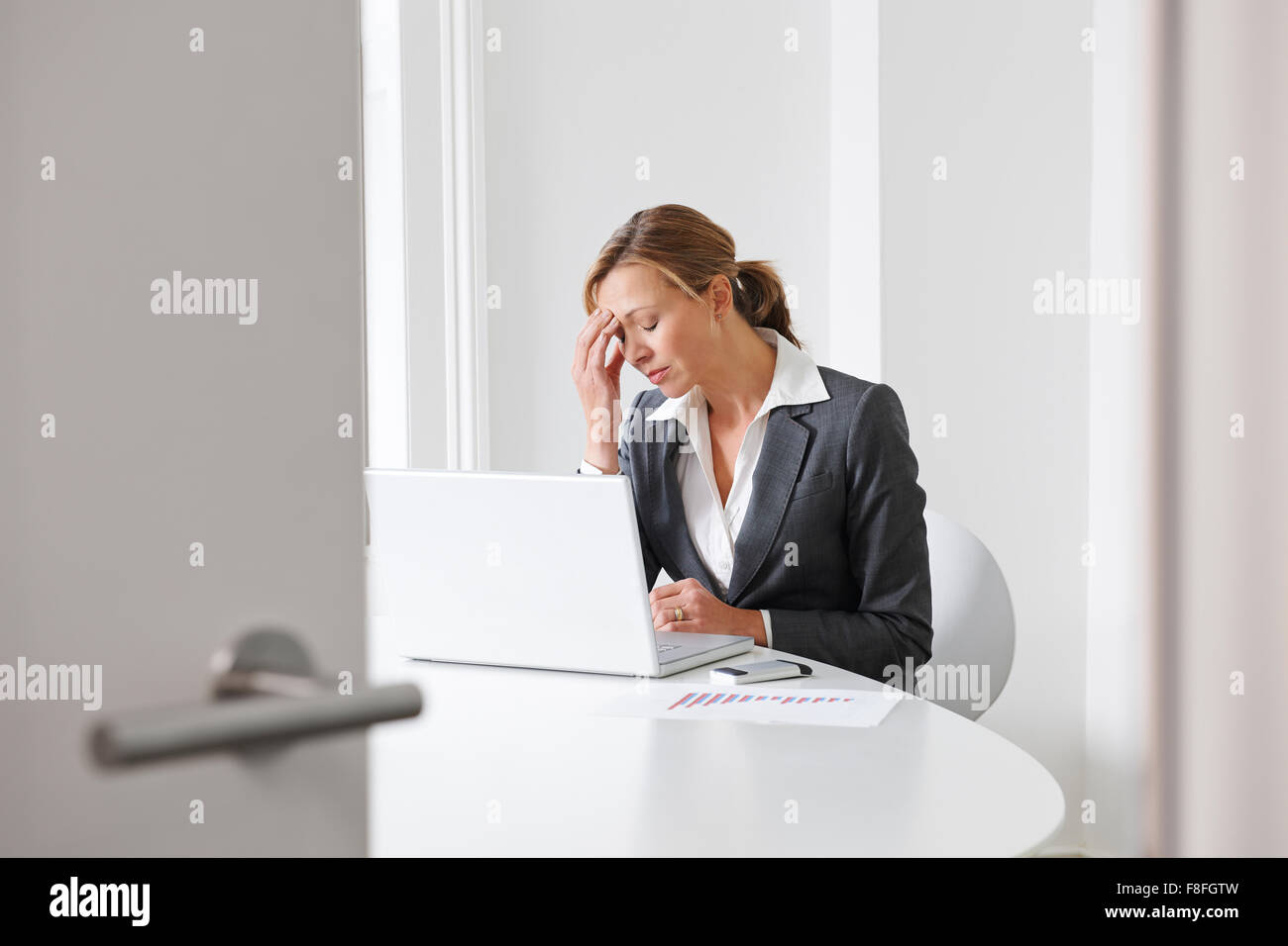 Stressed Businesswoman Working In Office - Stock Image