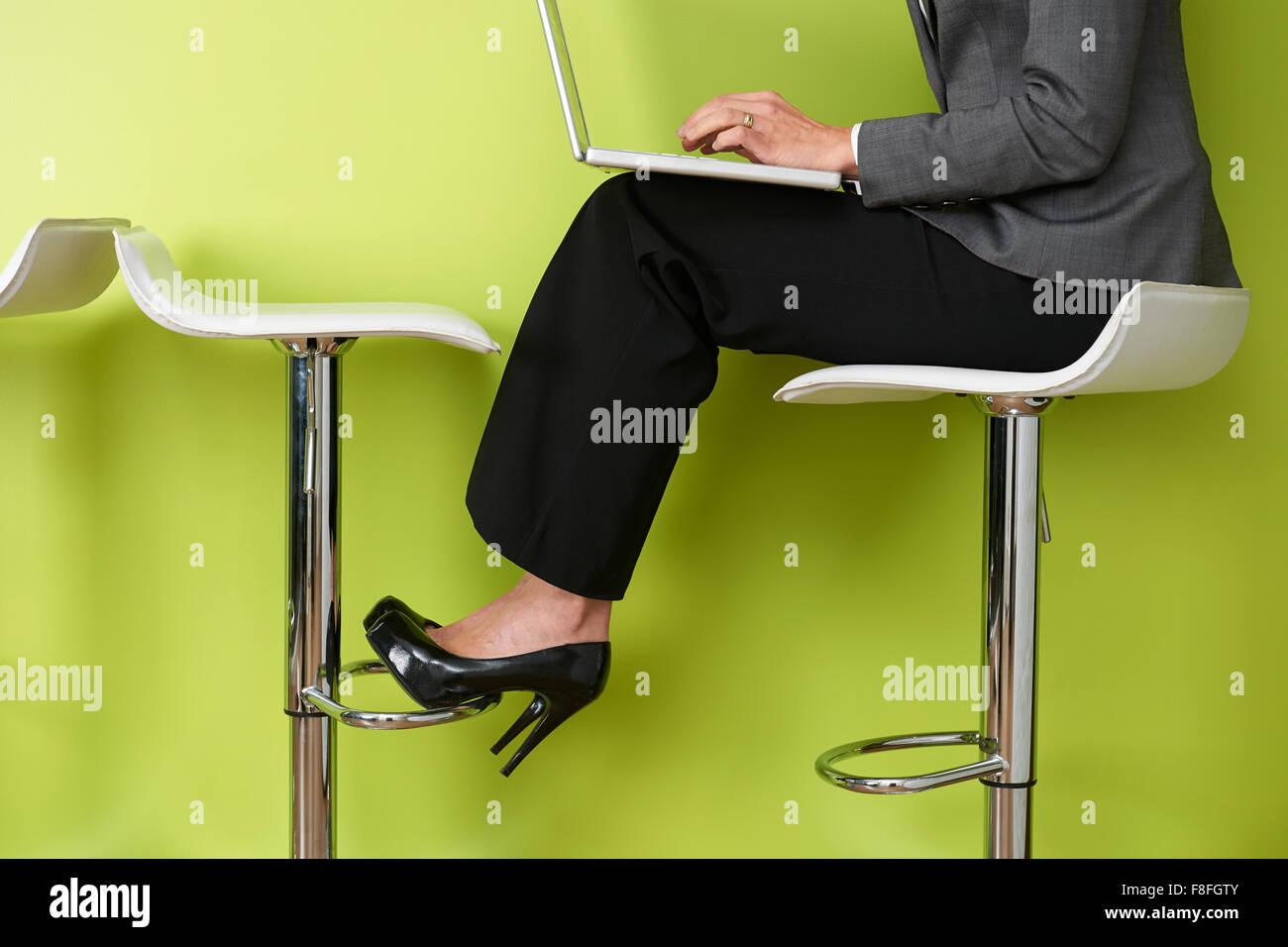 Close Up Of Businesswoman Sitting On Stool Using Laptop - Stock Image
