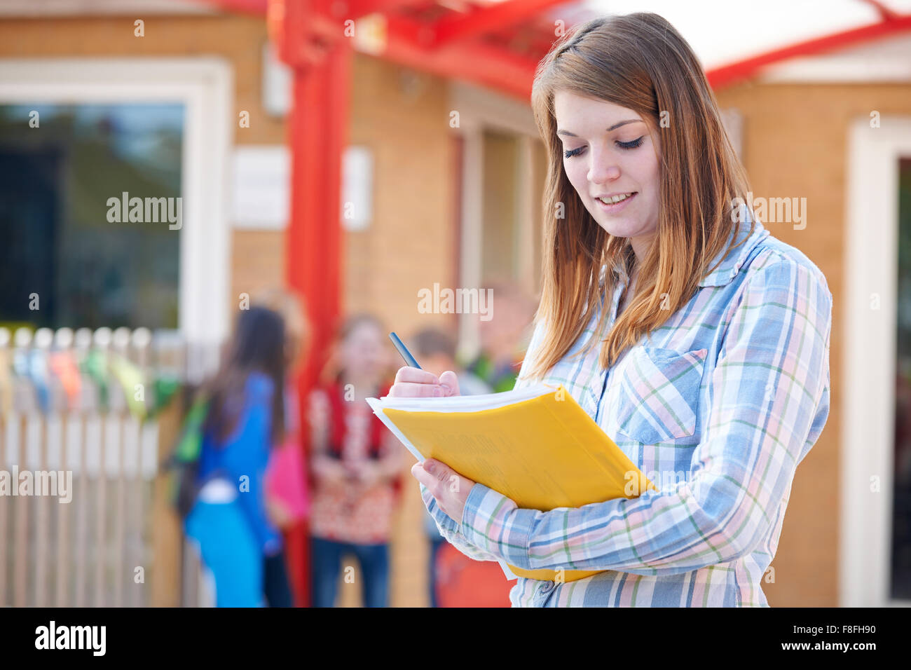 School Teacher Making Notes In Playground - Stock Image
