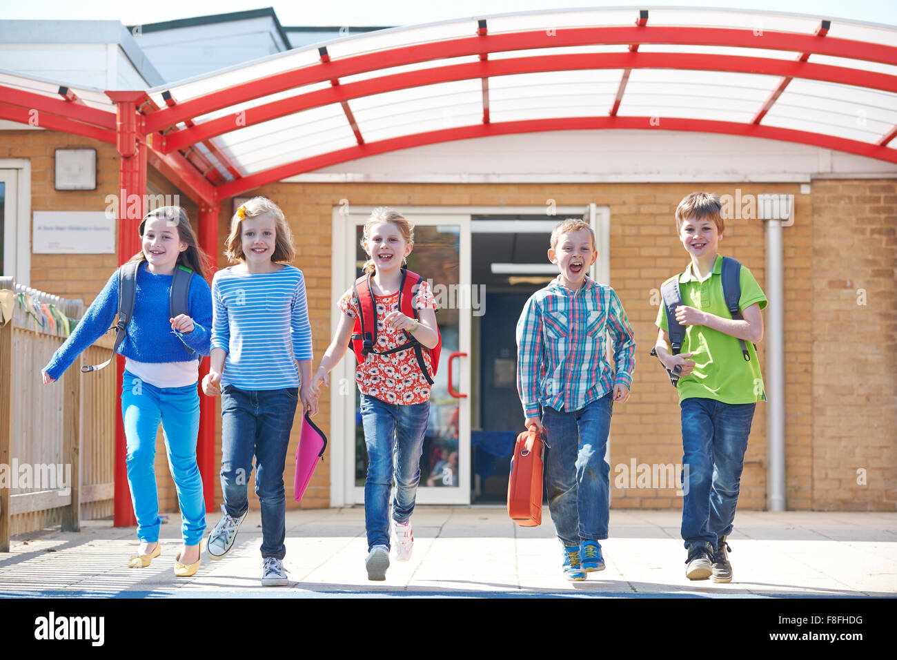 Schoolchildren Running Into Playground At End Of Class - Stock Image
