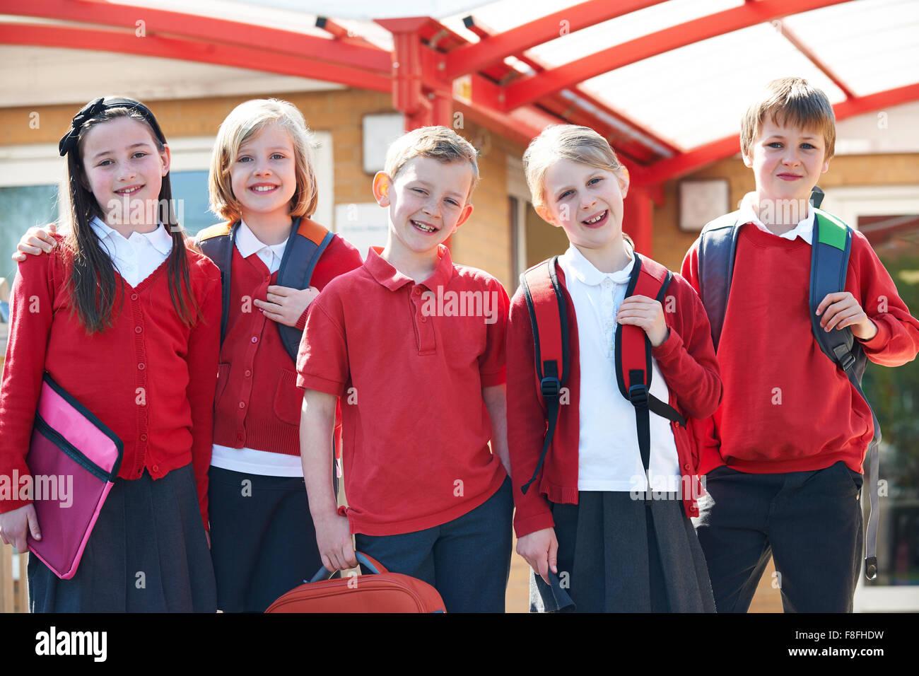 Portrait Of Schoolchildren Outside Classroom Carrying Bags - Stock Image