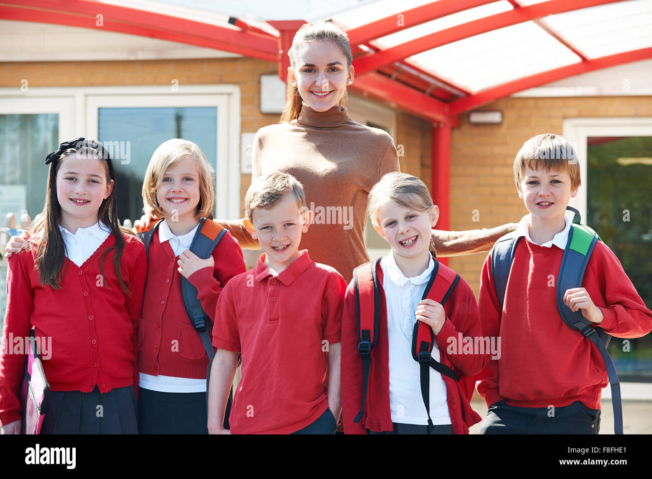 Group Of Schoolchildren With Teacher In Playground - Stock Image