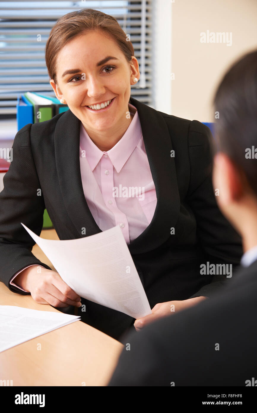 Female Businesswoman Interviewing Male Job Candidate - Stock Image