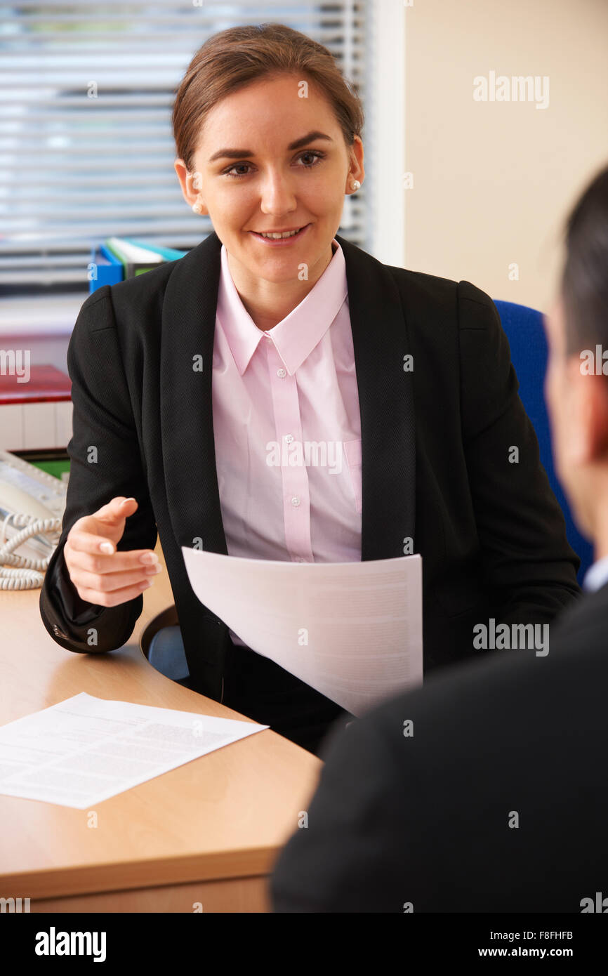 Businesswoman Interviewing Male Job Candidate - Stock Image