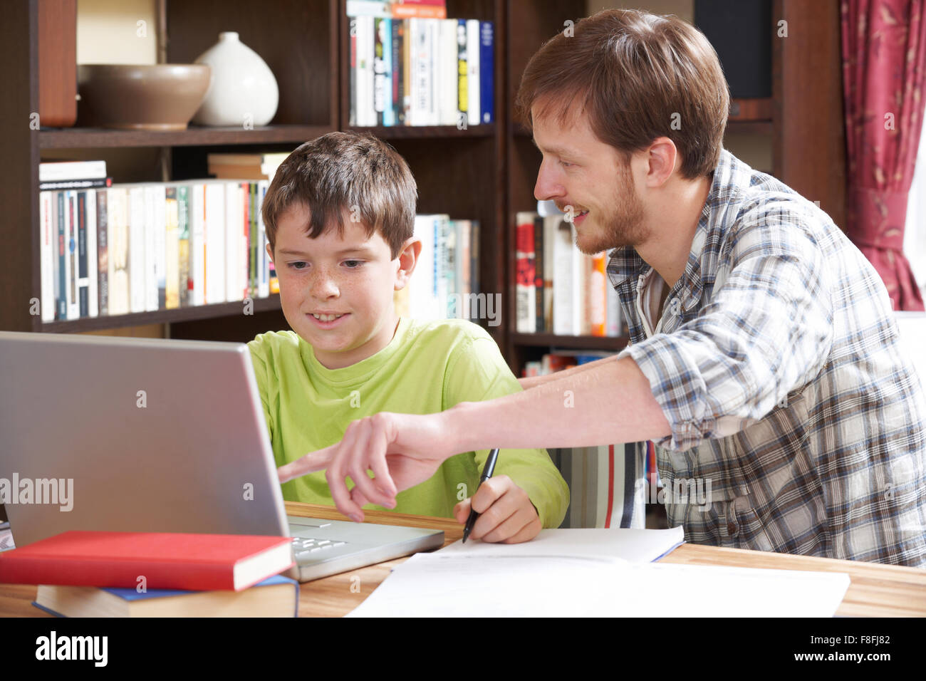 Boy Studying With Home Tutor - Stock Image