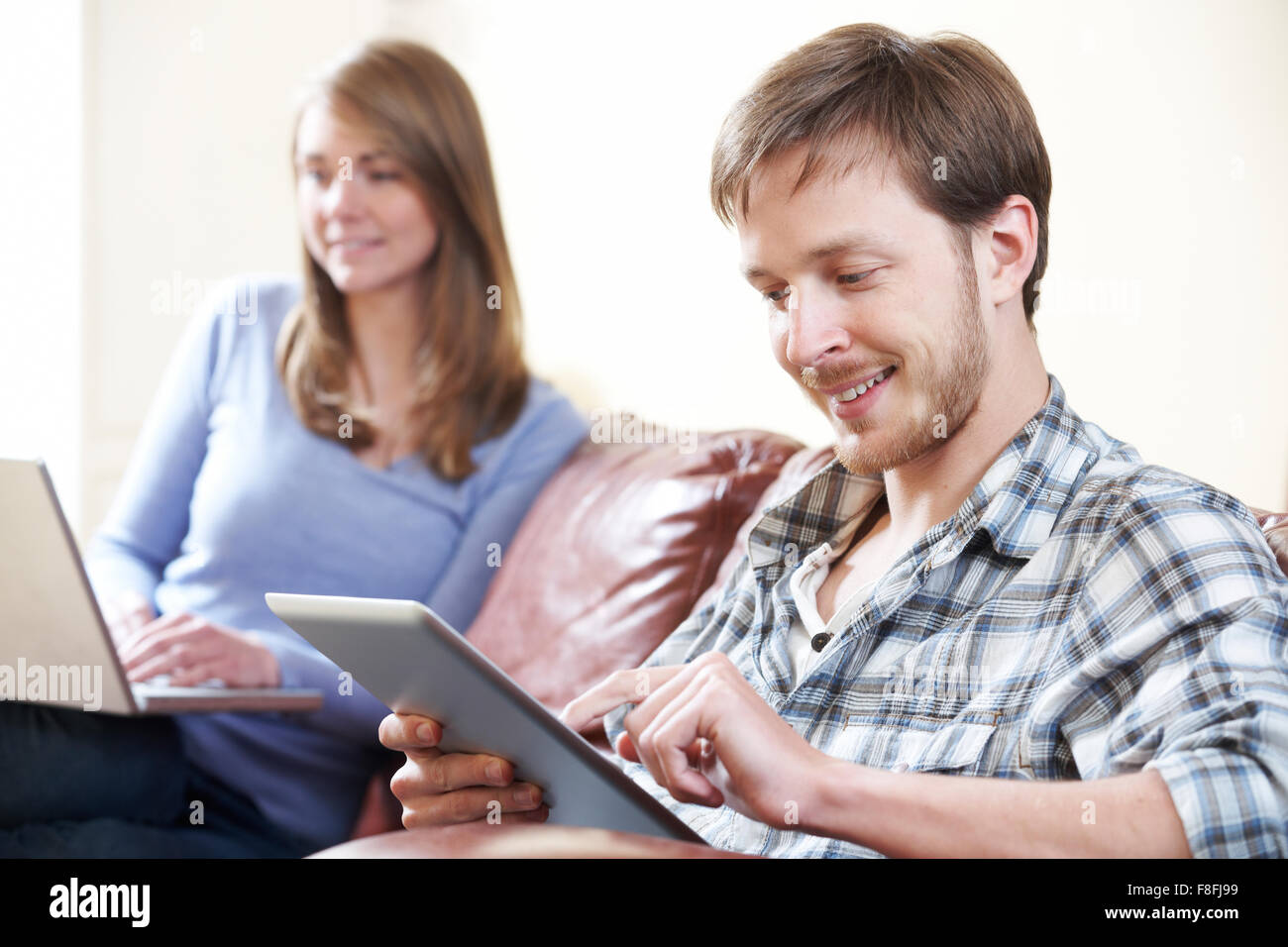 Couple Using Digital Technology At Home - Stock Image