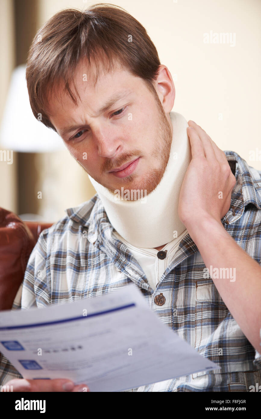 Man Wearing Surgical Collar Reading Letter - Stock Image