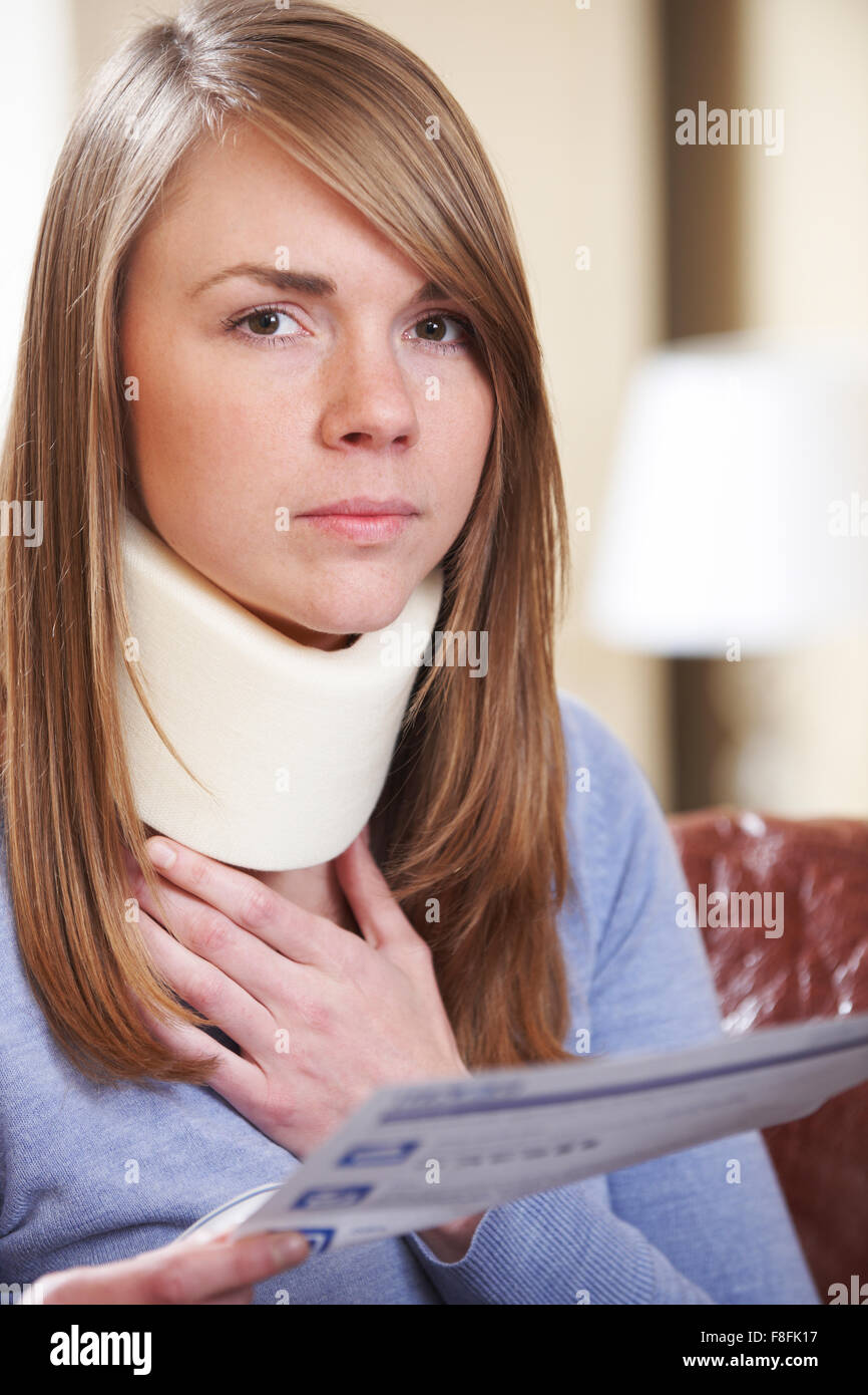 Young Woman Wearing Neck Brace Reading Letter - Stock Image