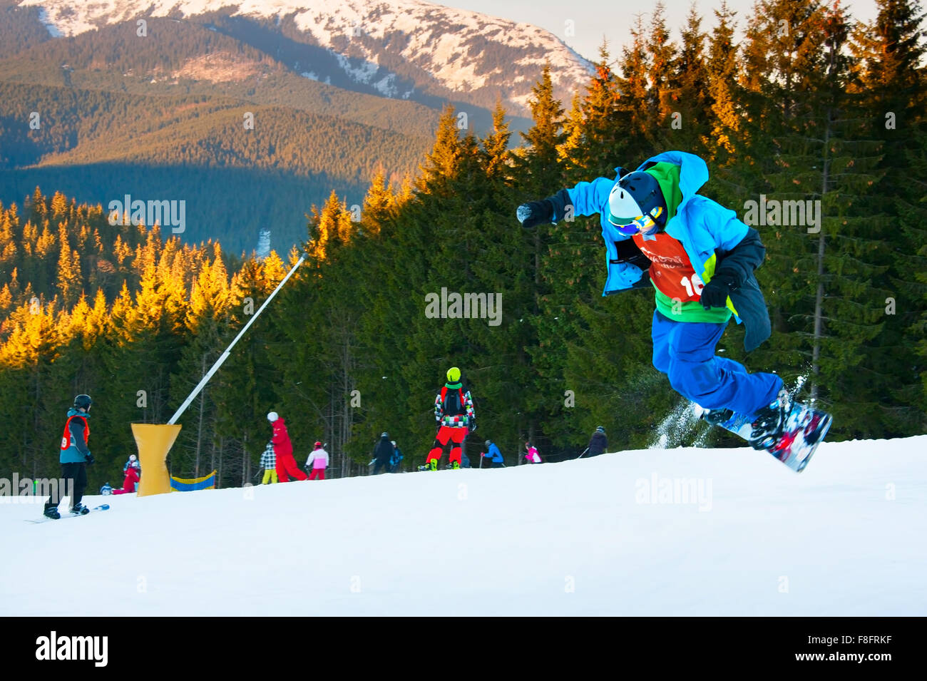 Snowboarder jumping in Bukovel ski resort. Bukovel is the most popular ski resort in Ukraine. - Stock Image