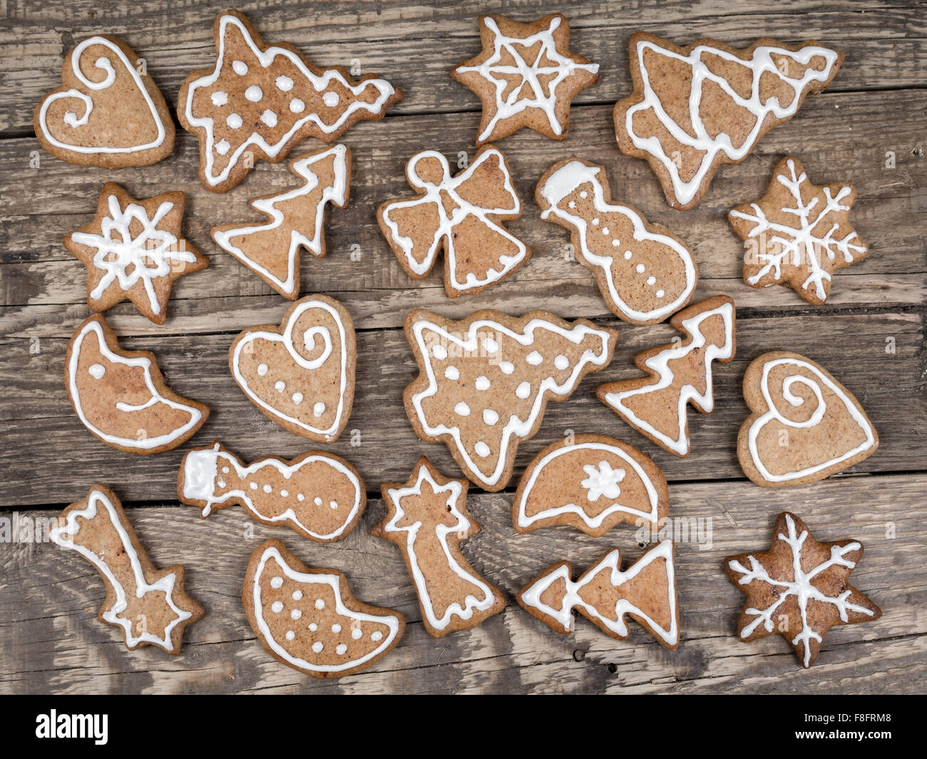 8eee5c5fc208d Different shape Christmas gingerbread cookies with white icing placed on  wooden rustic boards