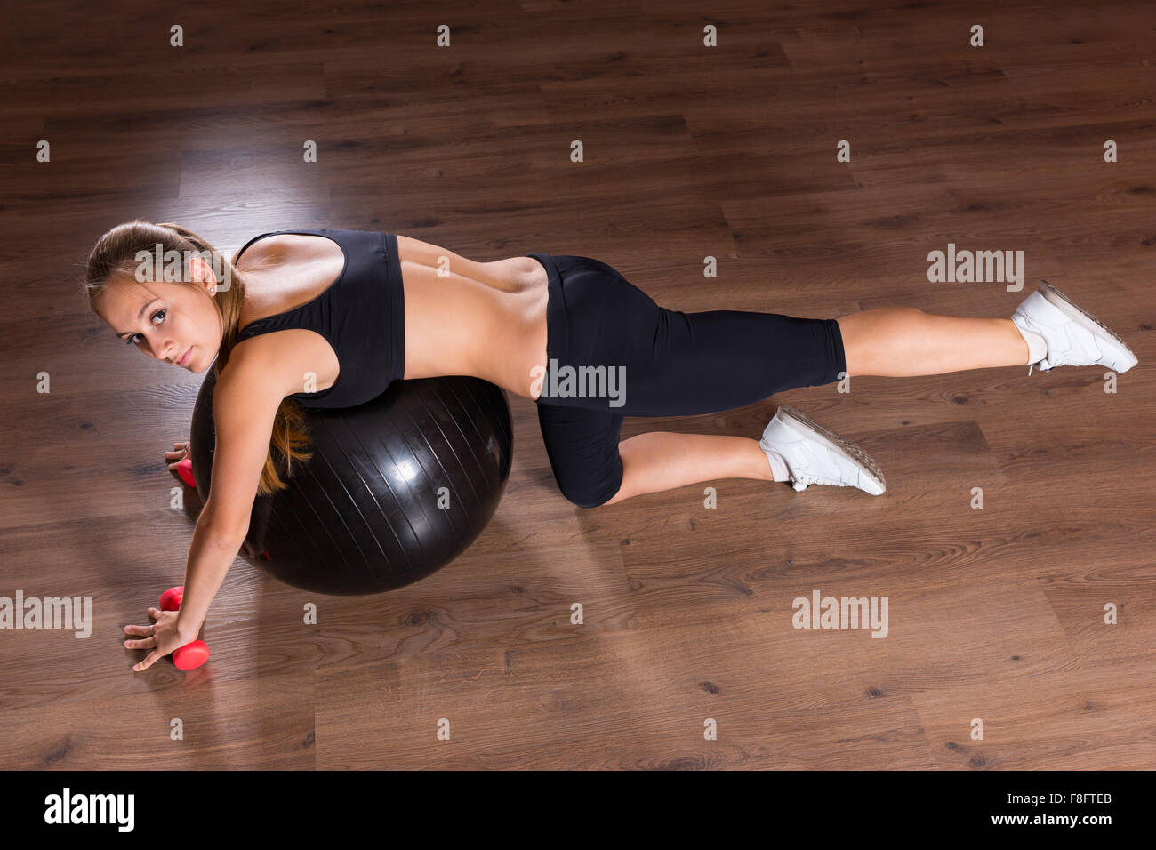 High Angle Full Length View of Young Woman Looking Up at Camera and Performing Leg Lift Core Strengthening Exercises - Stock Image