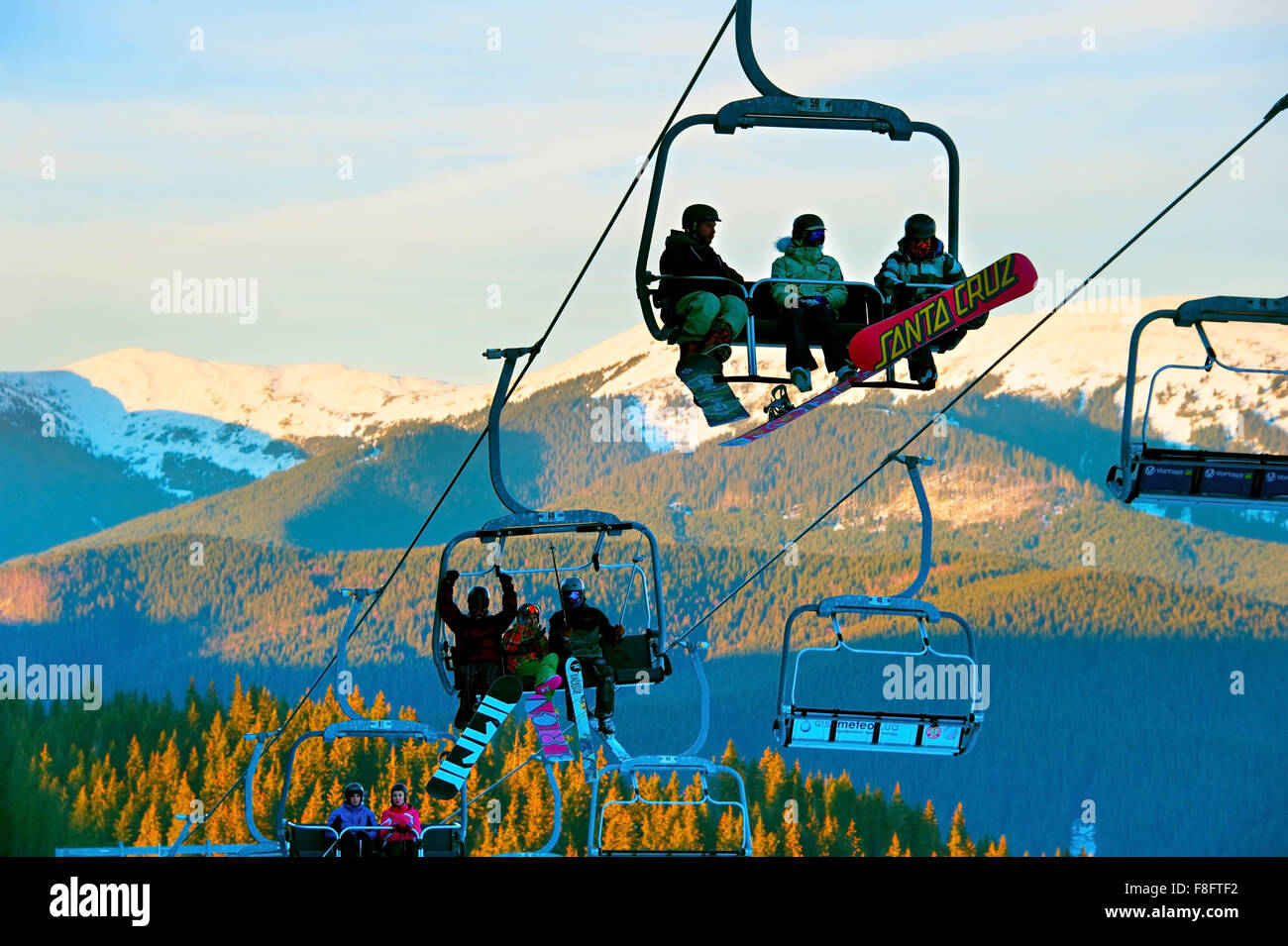 People on a ski lift in Bukovel. Bukovel is the most popular ski resort in Ukraine. - Stock Image