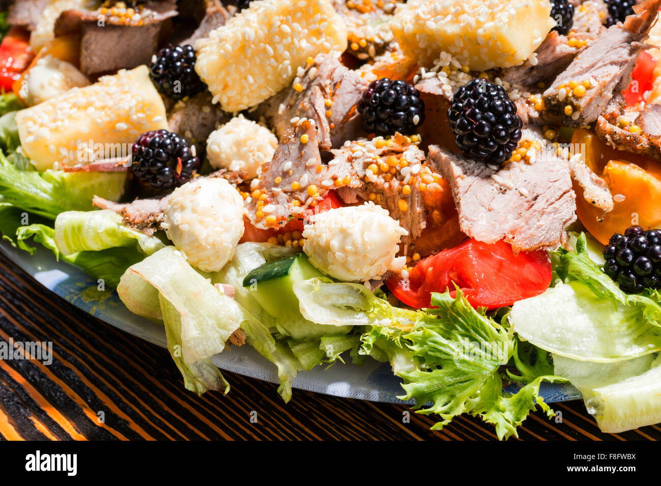 Close Up of Gourmet Salad Made with Fresh Fruit and Vegetables, Variety of Cheeses and Meats on Rustic Wooden Table Stock Photo