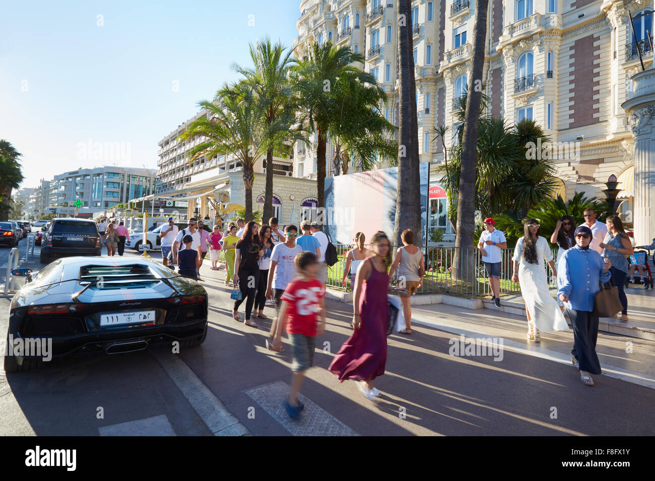 People walking in a summer afternoon along the Croisette boulevard in Cannes near Intercontinental Carlton hotel - Stock Image