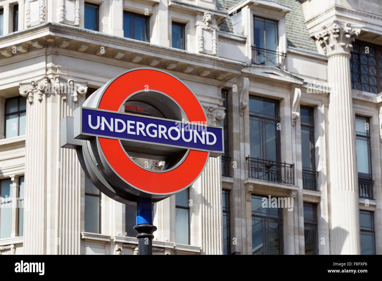 Famous London underground sign with architecture background - Stock Image