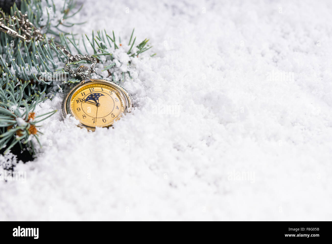 new year background with green pine branches and a vintage yellow clock on white snow at midnight