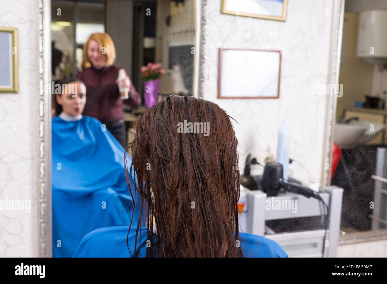 Close Up Rear View of Brunette Woman with Wet Hair Sitting in Chair in Salon with Reflection of Stylist and Woman - Stock Image