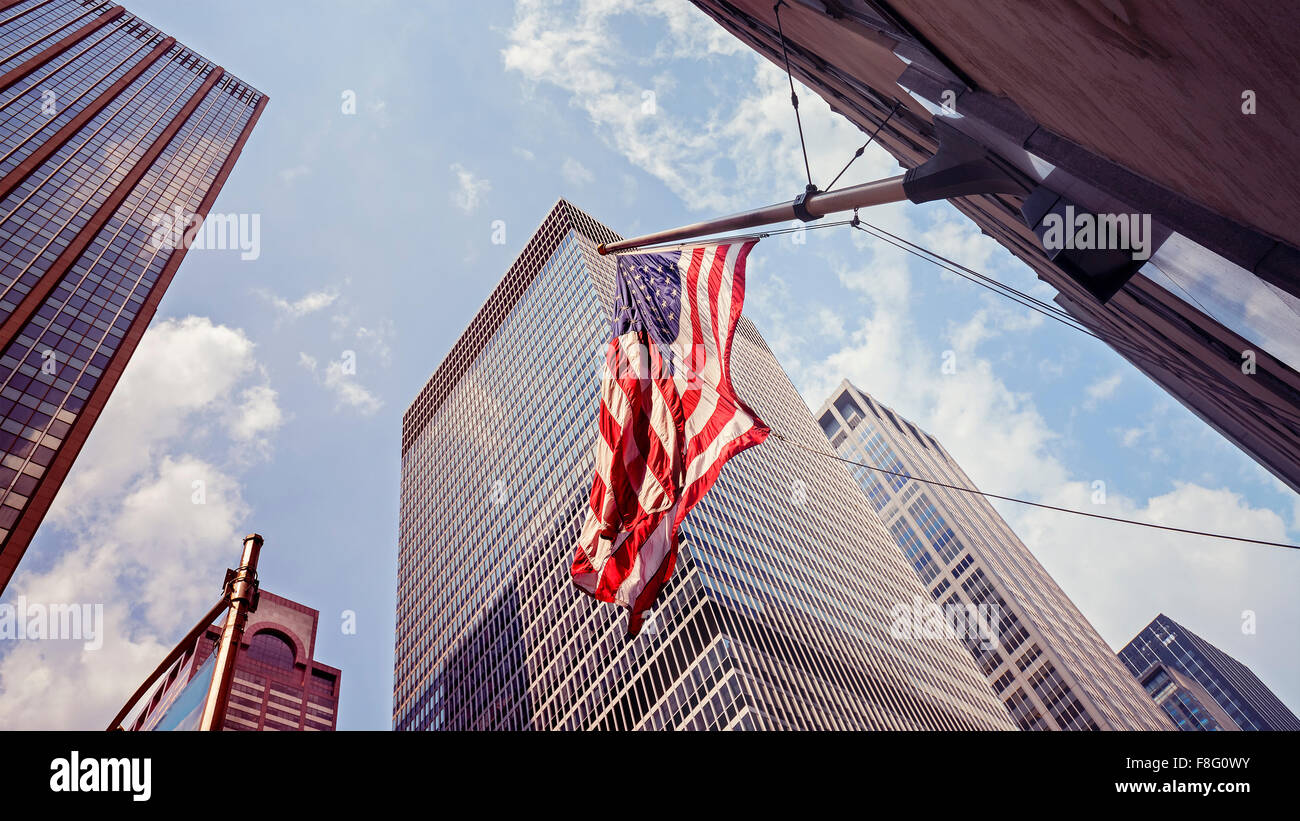 Vintage toned American flag and skyscrapers in Manhattan, New York City, USA. - Stock Image