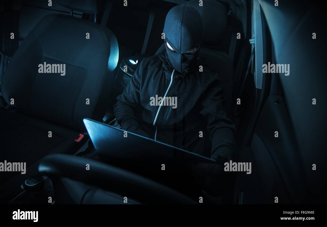 Hacking Car Systems. Hacker with His Computer at Work. - Stock Image