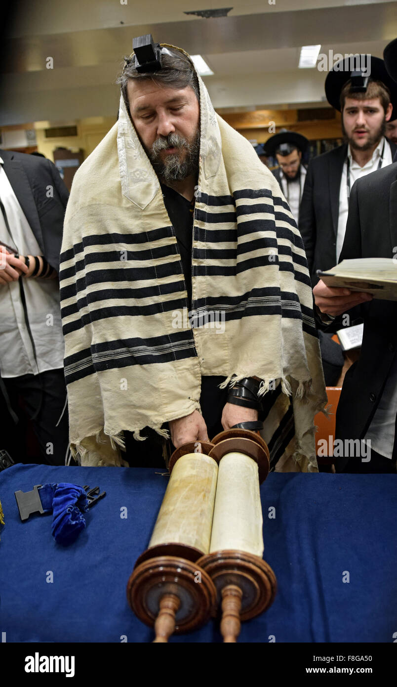 A religious Jewish man blessing the Torah at morning services at a synagogue in Brooklyn, New York. - Stock Image