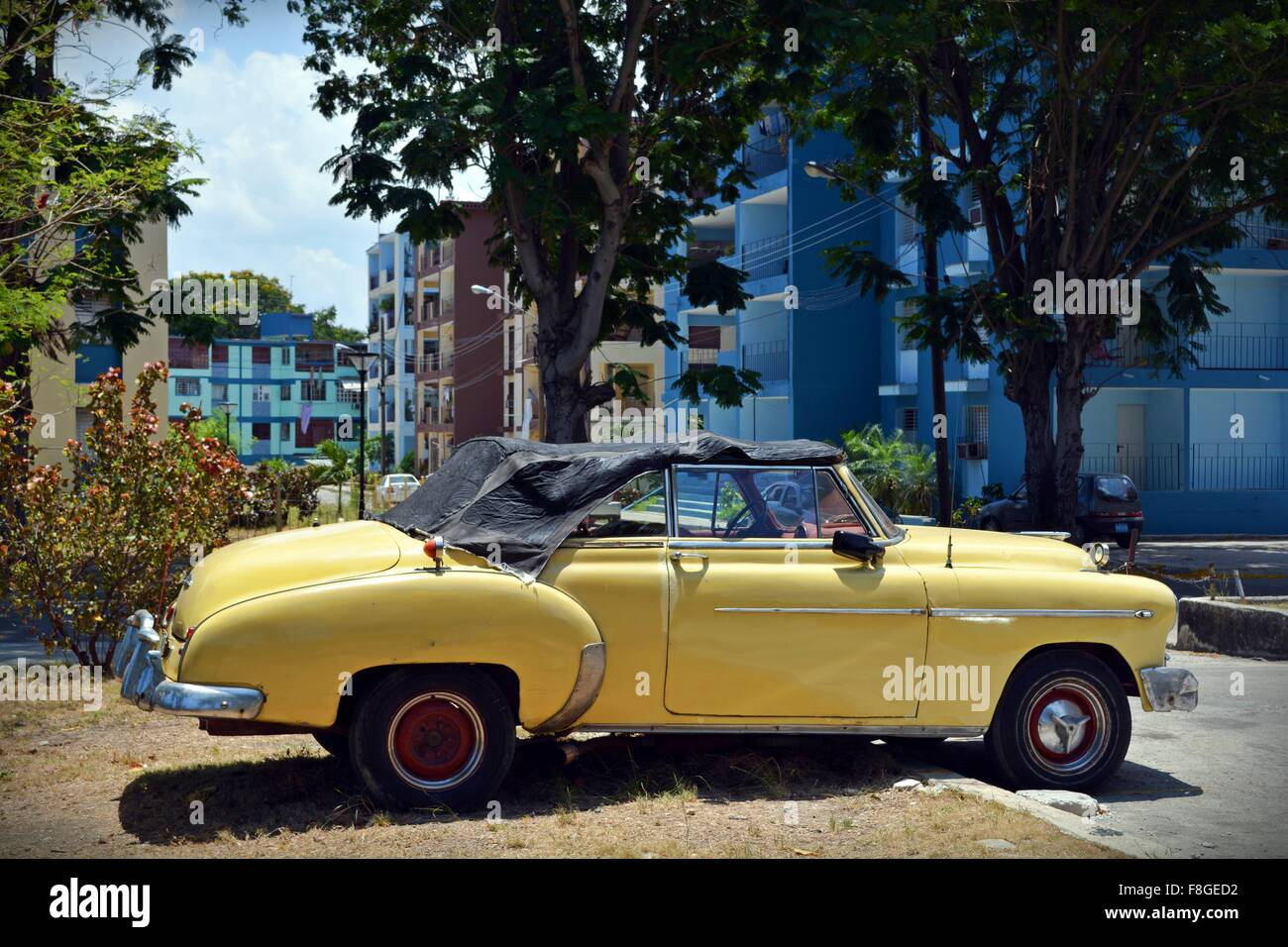 beat up vintage yellow soft top car parked badly in a residential street in Havana Cuba - Stock Image