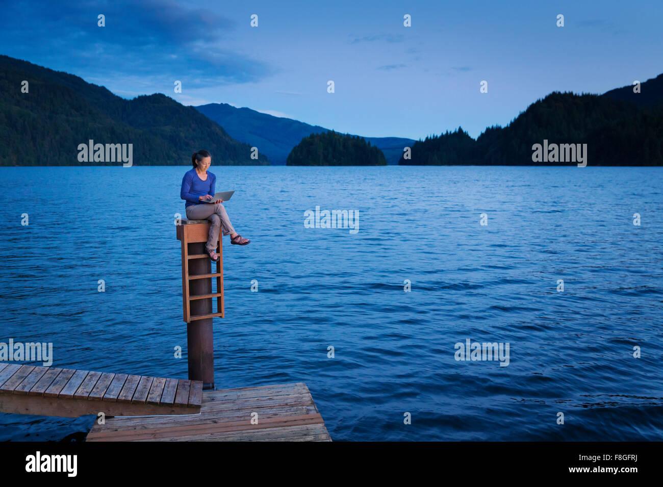 Japanese woman sitting on wooden dock at lake Stock Photo