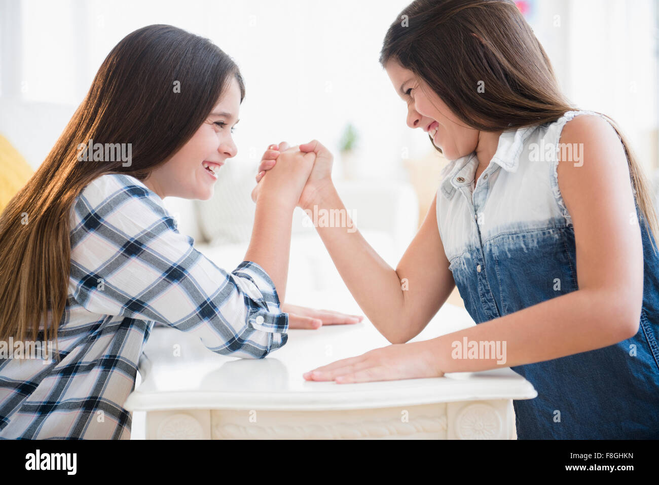 Caucasian twin sisters arm wrestling Stock Photo