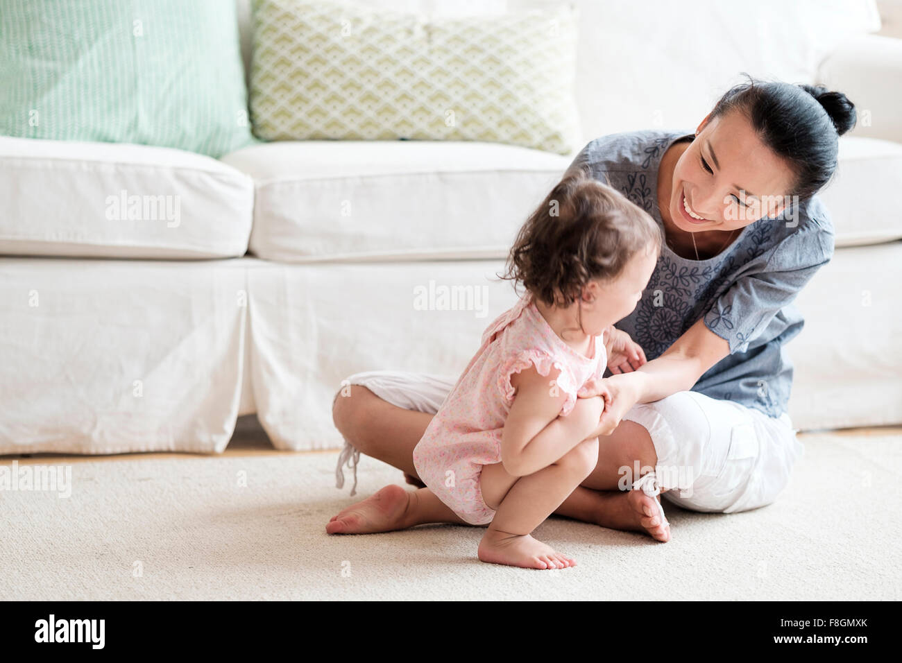 Mother and baby daughter playing in living room Stock Photo