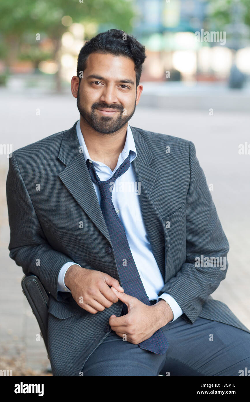 Indian businessman sitting on bench in city Stock Photo