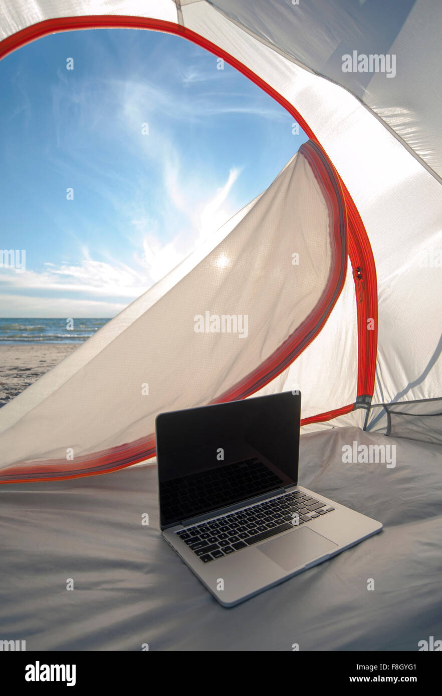 Laptop in camping tent on beach - Stock Image