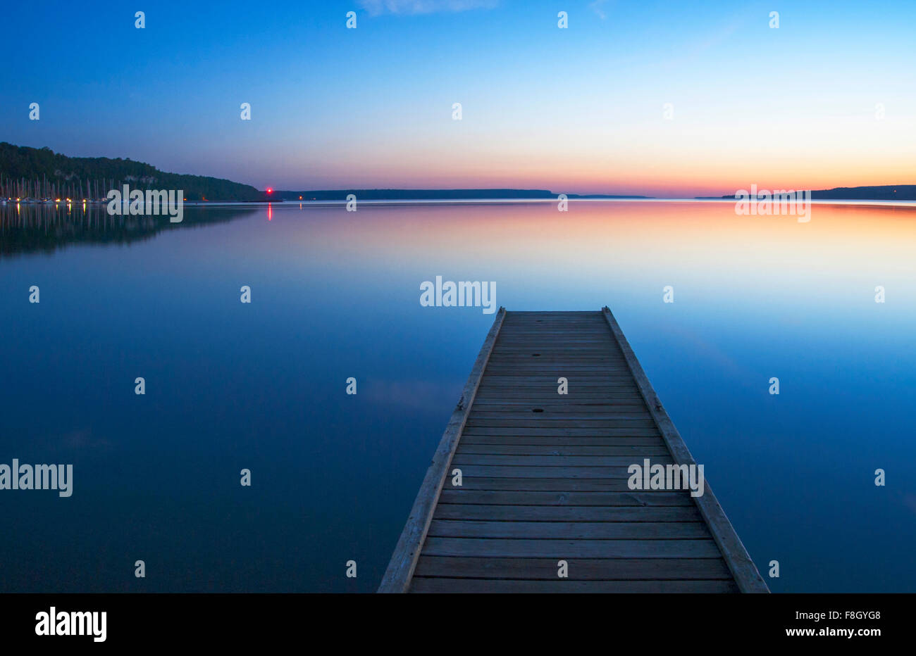 Wooden dock over still lake - Stock Image